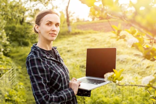 Donna con un computer portatile in fattoria