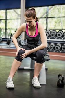 Donna con un ginocchio infortunato seduto in palestra