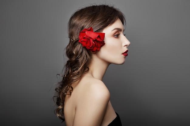Donna con un grande fiore rosso nei capelli. capelli castani