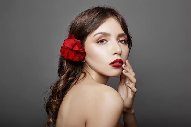 Donna con un grande fiore rosso tra i capelli