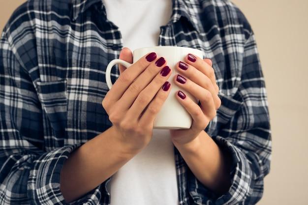 Donna con un manicure borgogna in camicia a quadri che tiene tazza bianca