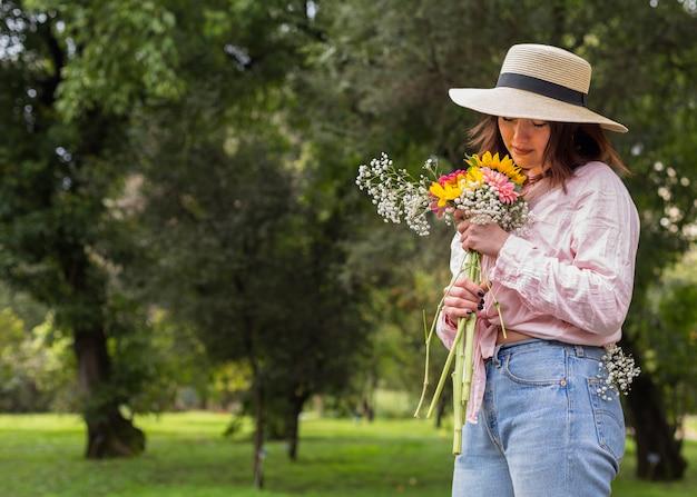 Donna con un mazzo di fiori nel parco