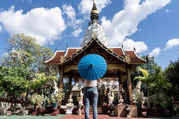 Donna con un ombrello blu di fronte a un tempio buddista