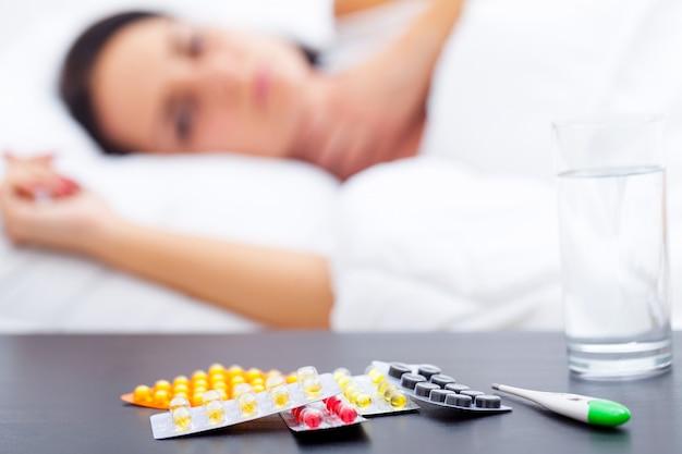 Donna con un raffreddore sul letto sotto la coperta
