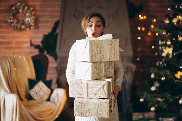 Donna con un sacco di regali davanti all'albero di natale
