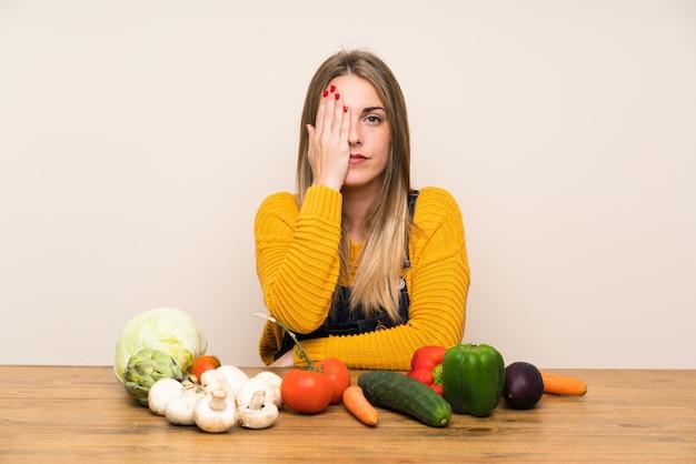 Donna con un sacco di verdure che coprono un occhio a mano