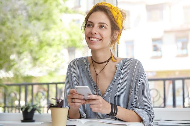 Donna con un sorriso affascinante seduto in terrazza con il libro