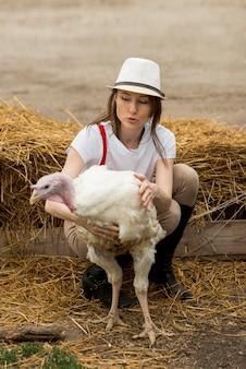 Donna con un tacchino in una fattoria