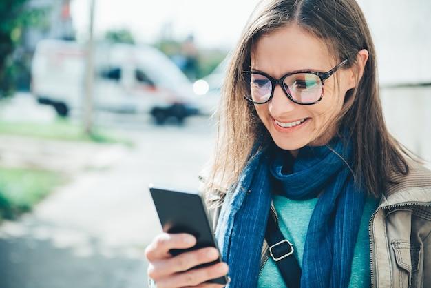 Donna con un telefono cellulare sulla strada