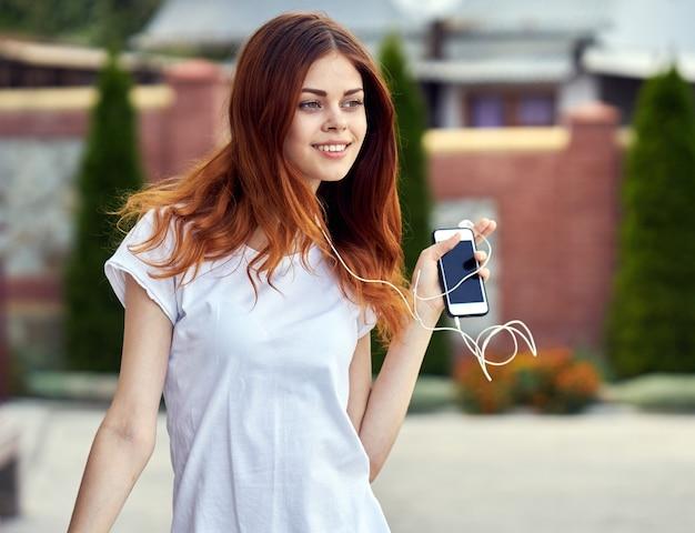 Donna con un telefono in cuffia corre