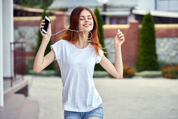 Donna con un telefono nelle esecuzioni delle cuffie