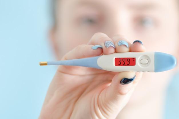 Donna con un termometro in mano. aumento della temperatura corporea faccia sullo sfondo