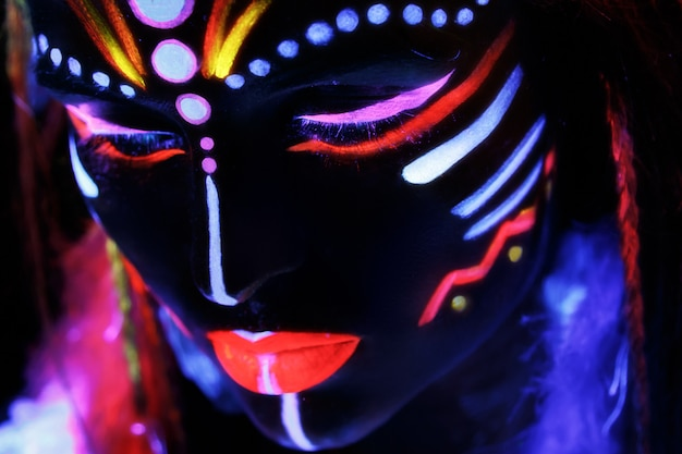 Donna con un trucco al neon alla luce ultravioletta