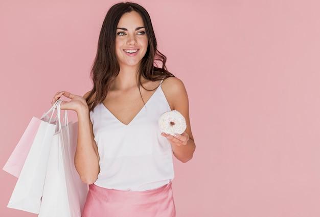 Donna con una ciambella con cioccolata bianca su sfondo rosa