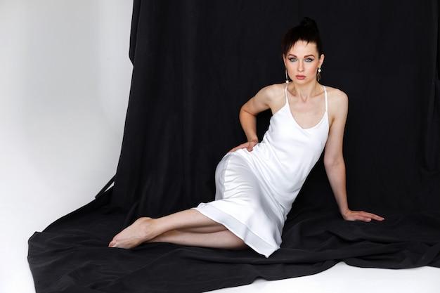 Donna con una figura snella si siede su uno sfondo di tessuto nero in studio.