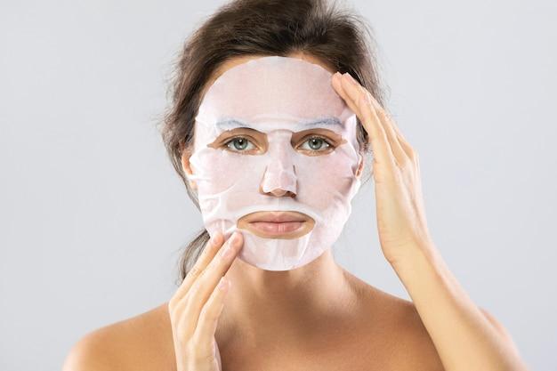 Donna con una maschera idratante dello strato sul suo fronte isolato su gray
