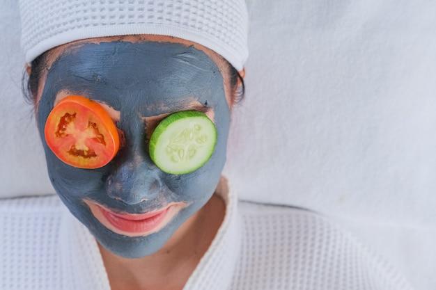Donna con una maschera per il viso, con cetrioli e pomodori sugli occhi.