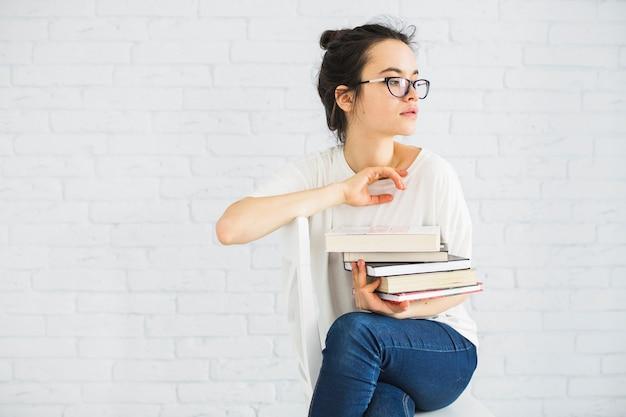 Donna con una pila di libri sulla sedia