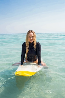 Donna con una tavola da surf in una giornata di sole