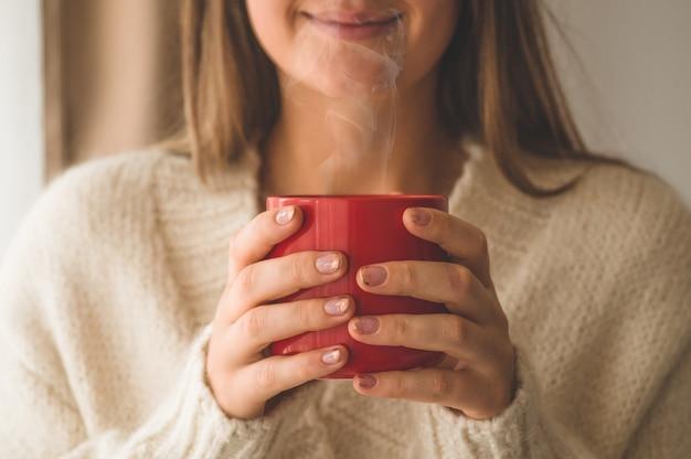 Donna con una tazza di bevanda calda vicino alla finestra. buongiorno con il tè. autunno inverno