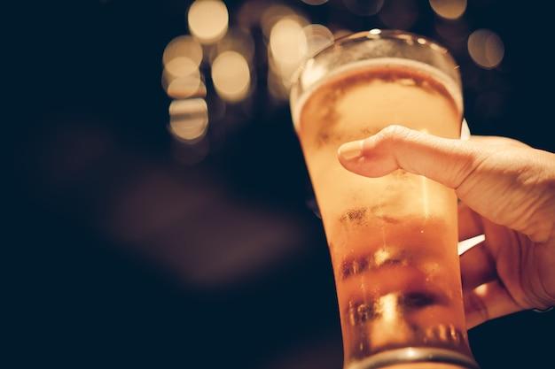 Donna con unghie giallo lucido tenendo un bicchiere di birra fredda con un bel bokeh, tono scuro