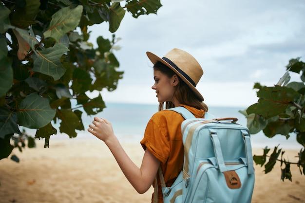 Donna con uno zaino blu in un abito giallo e cappello cammina lungo l'oceano lungo la sabbia con le palme