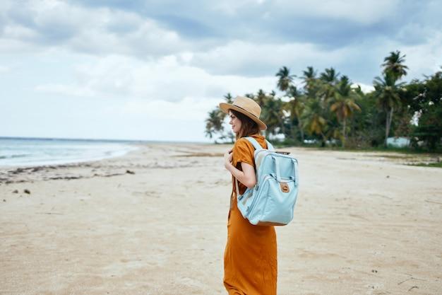 Donna con uno zaino blu in un abito giallo e cappello cammina lungo la sabbia con le palme