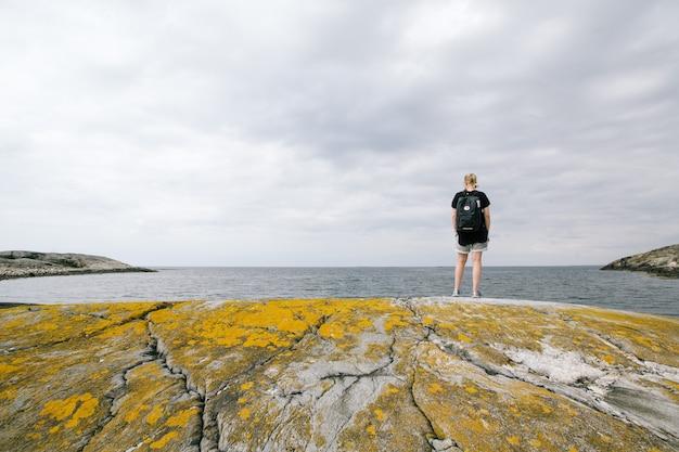 Donna con uno zaino che sta su una roccia vicino al mare con un cielo nuvoloso