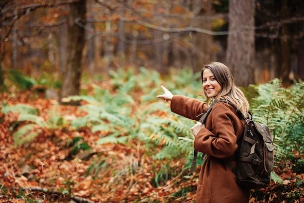 Donna con uno zaino nella foresta di autunno
