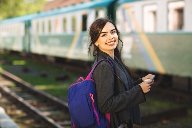 Donna con uno zaino, vicino al treno controlla il suo biglietto per la piattaforma della stazione