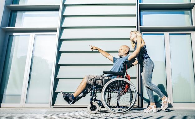 Donna con uomo disabile che appende intorno