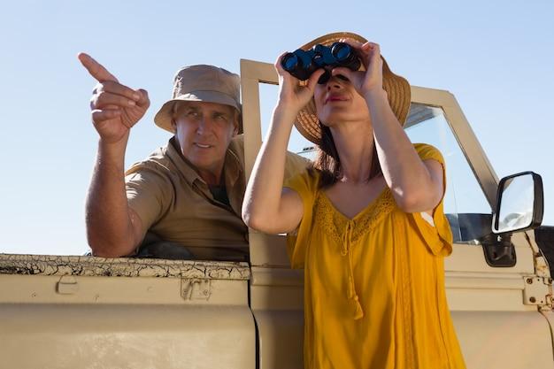 Donna con uomo guardando attraverso il binocolo