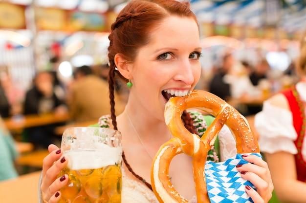 Donna con vestiti bavaresi tradizionali o dirndl in tenda da birra