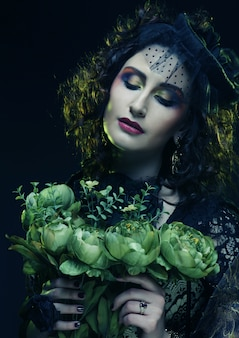 Donna con volto brigida che tiene grandi fiori verdi
