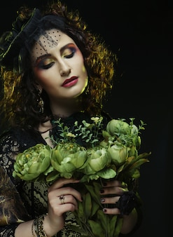 Donna con volto brigt che tiene grandi fiori verdi