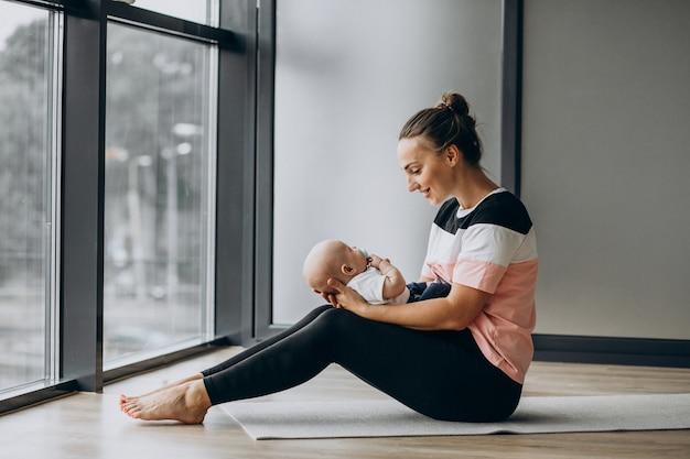 Donna con yoga di pratica del neonato