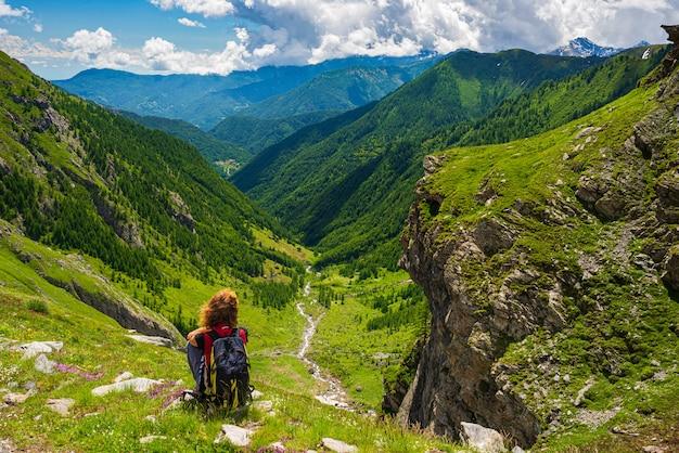 Donna con zaino appoggiato sulla cima della montagna, guardando vista