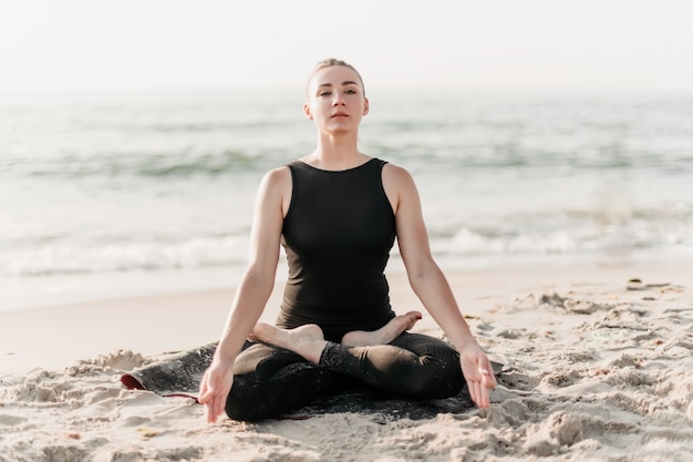 Donna concentrata che medita nella posa di yoga sulla spiaggia vicino all'oceano