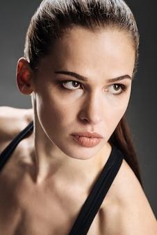 Donna concentrata che posa in abiti sportivi