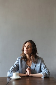 Donna concentrata che si siede all'interno vicino alla tazza di caffè