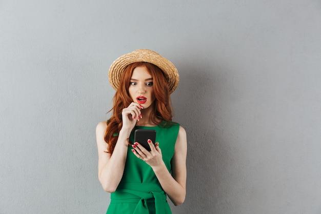 Donna confusa colpita giovani della testarossa che chiacchiera dal telefono.