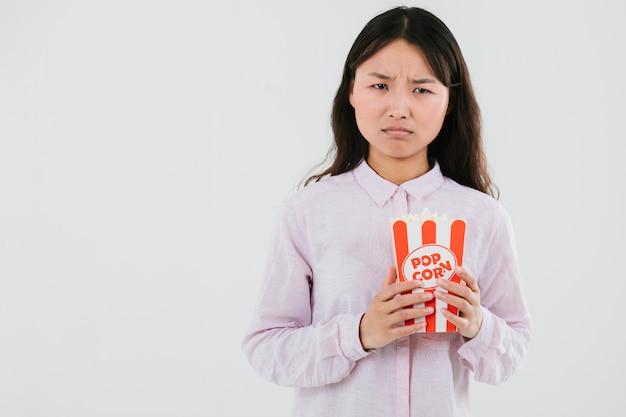 Donna confusa con un sacco di popcorn