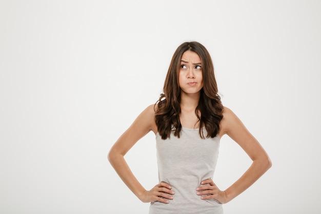 Donna confusa del brunette con le braccia sulle anche che osservano via sopra il grey