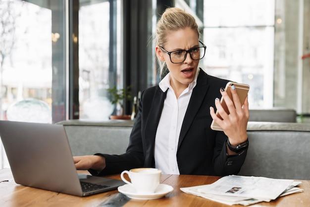 Donna confusa di affari che per mezzo del computer portatile e del telefono