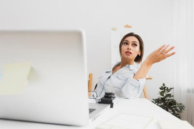 Donna confusa di vista frontale che si siede al suo scrittorio