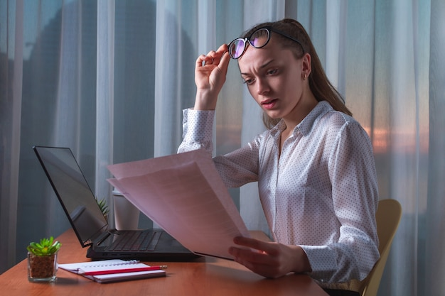 Donna confusa e frustrata di affari che ha problemi con documenti e rapporti.