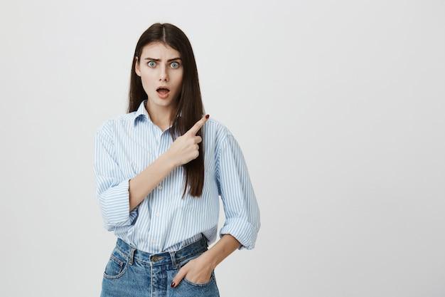 Donna confusa in camicia e jeans che punta nell'angolo in alto a destra