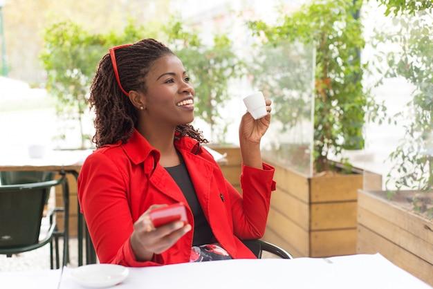 Donna contenta che beve caffè e utilizzando smartphone