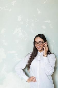 Donna contenta che parla sul telefono