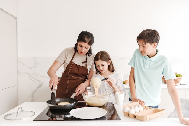 Donna contenta e bambini felici che cucinano insieme e frittelle sulla moderna stufa in cucina a casa